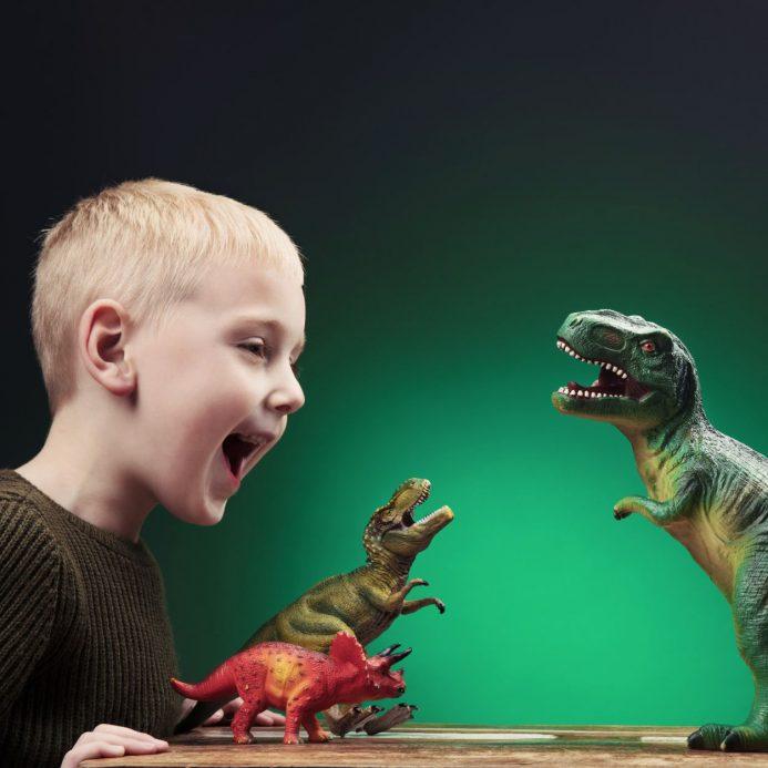 Child roaring at toy dinosaur